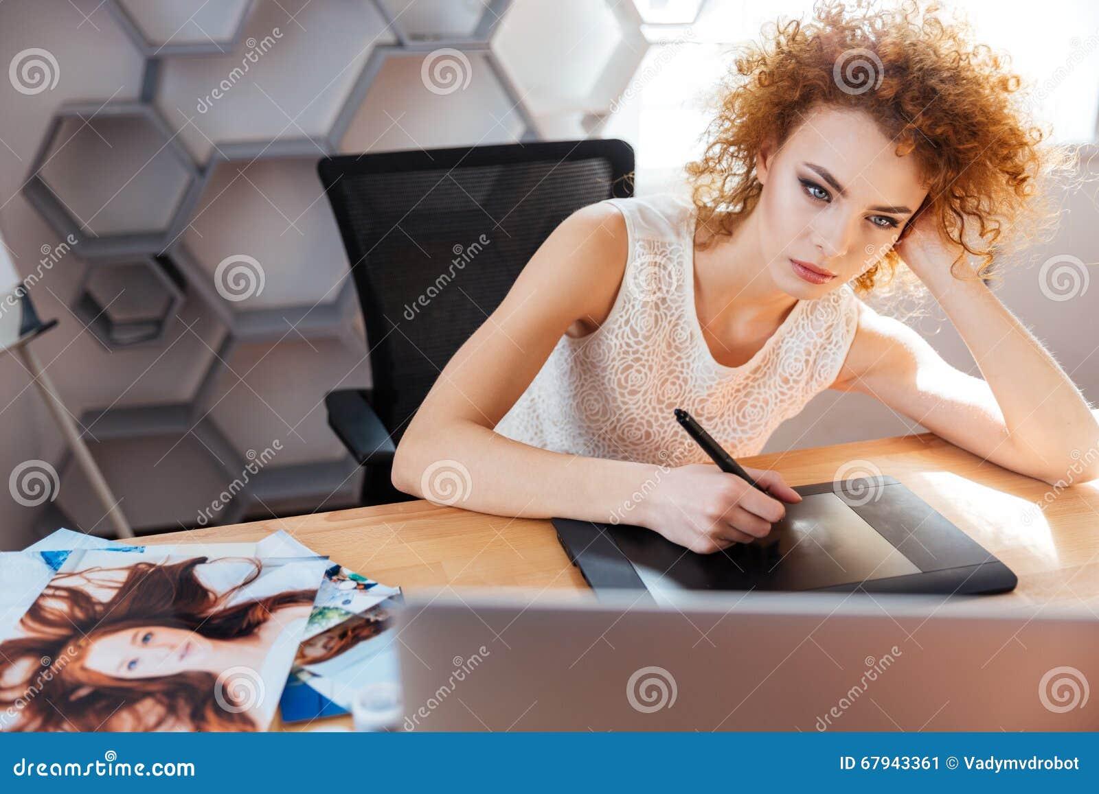 Skoncentrowany kobieta fotografa przerób obrazuje używać graficzną pastylkę w biurze