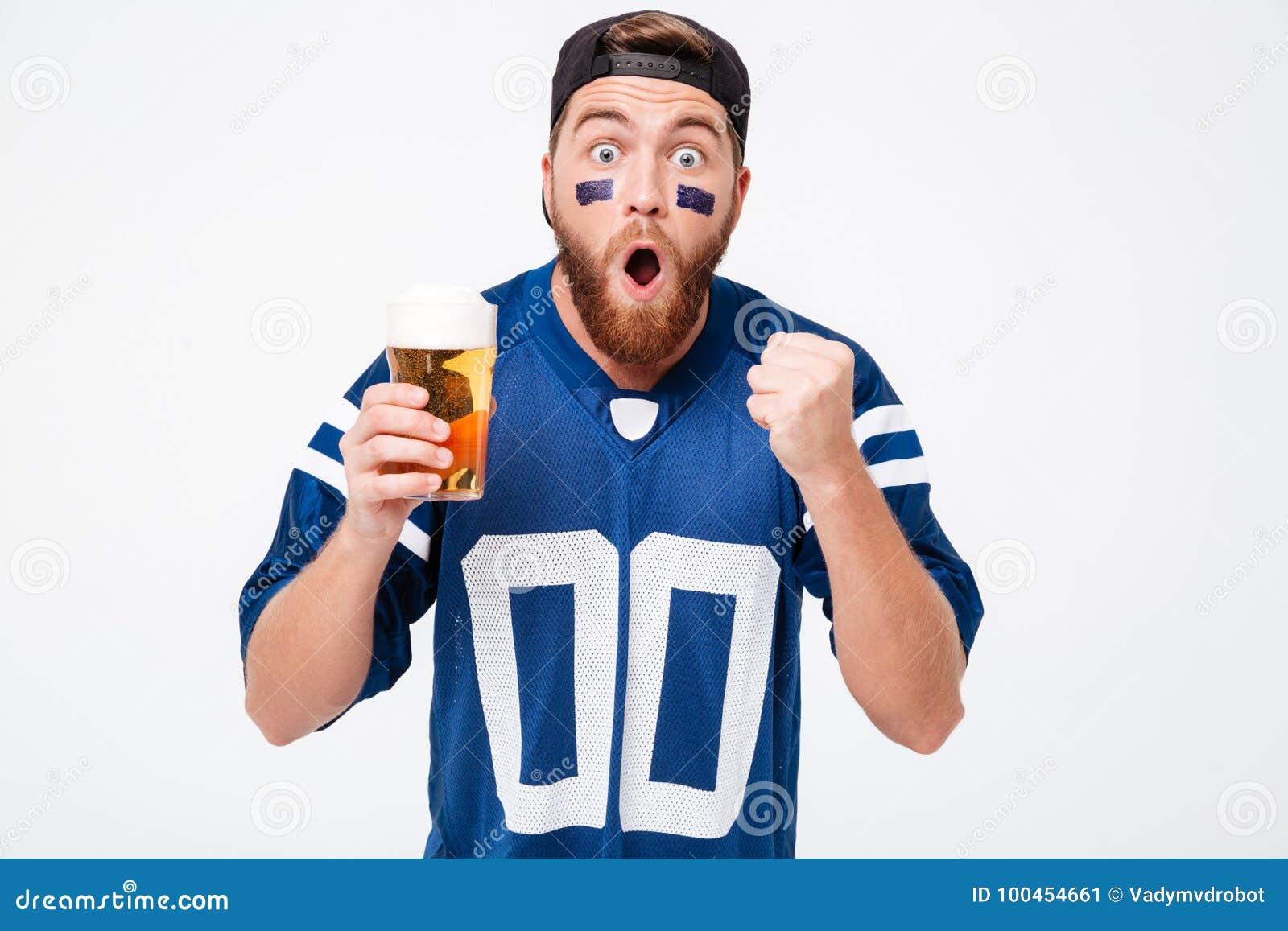 Skoncentrowany mężczyzna fan w błękitnej koszulce pije piwo