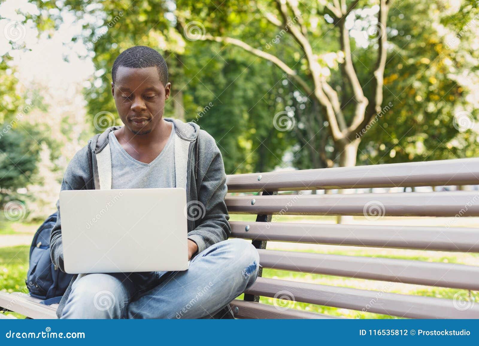 Skoncentrowany mężczyzna pracuje na jego laptopie outdoors