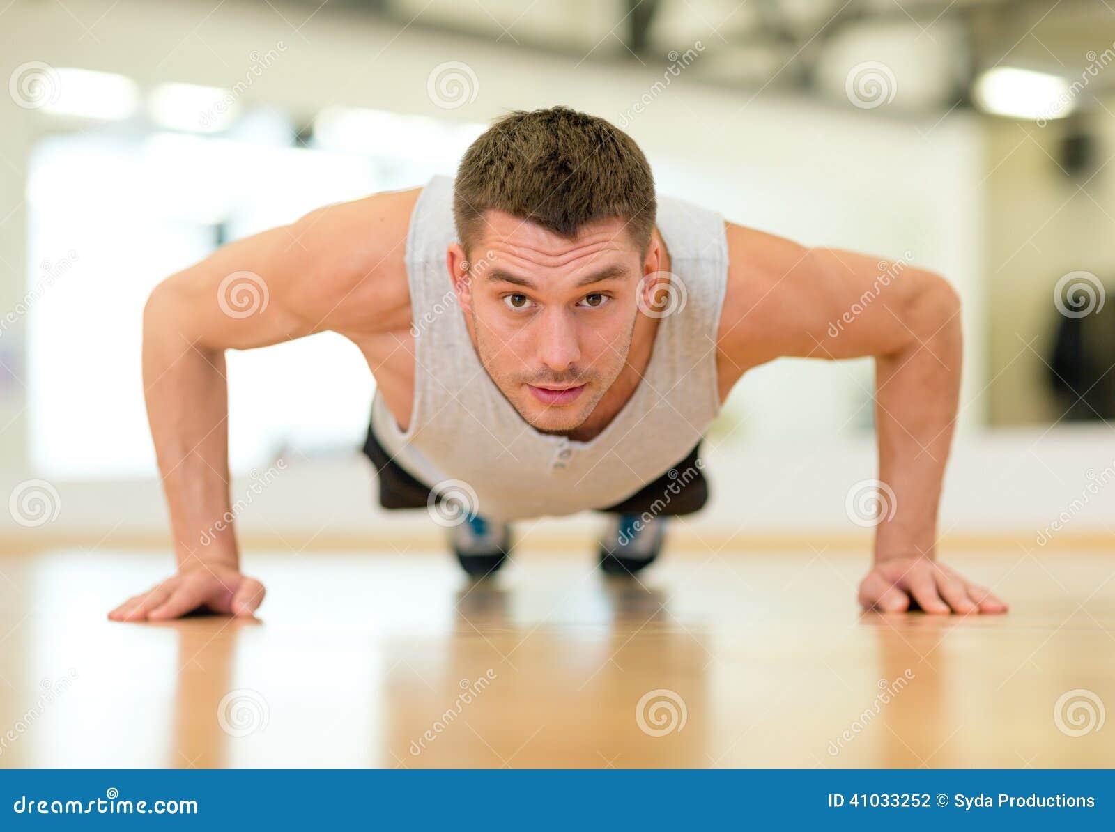 Skoncentrowany mężczyzna robi Ups w gym