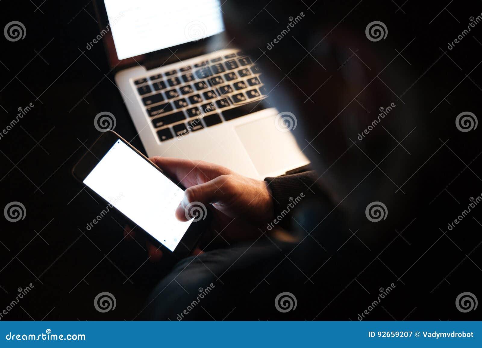 Skoncentrowany mężczyzna używa laptop i telefon