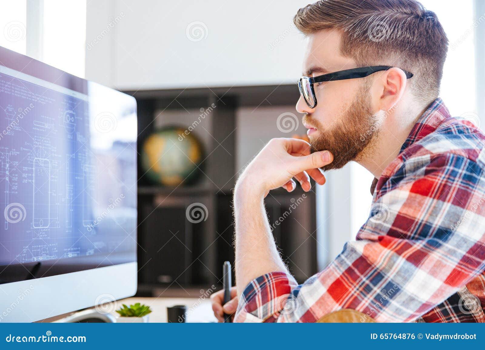 Skoncentrowany mężczyzna w szkłach rysuje projekty na komputerze