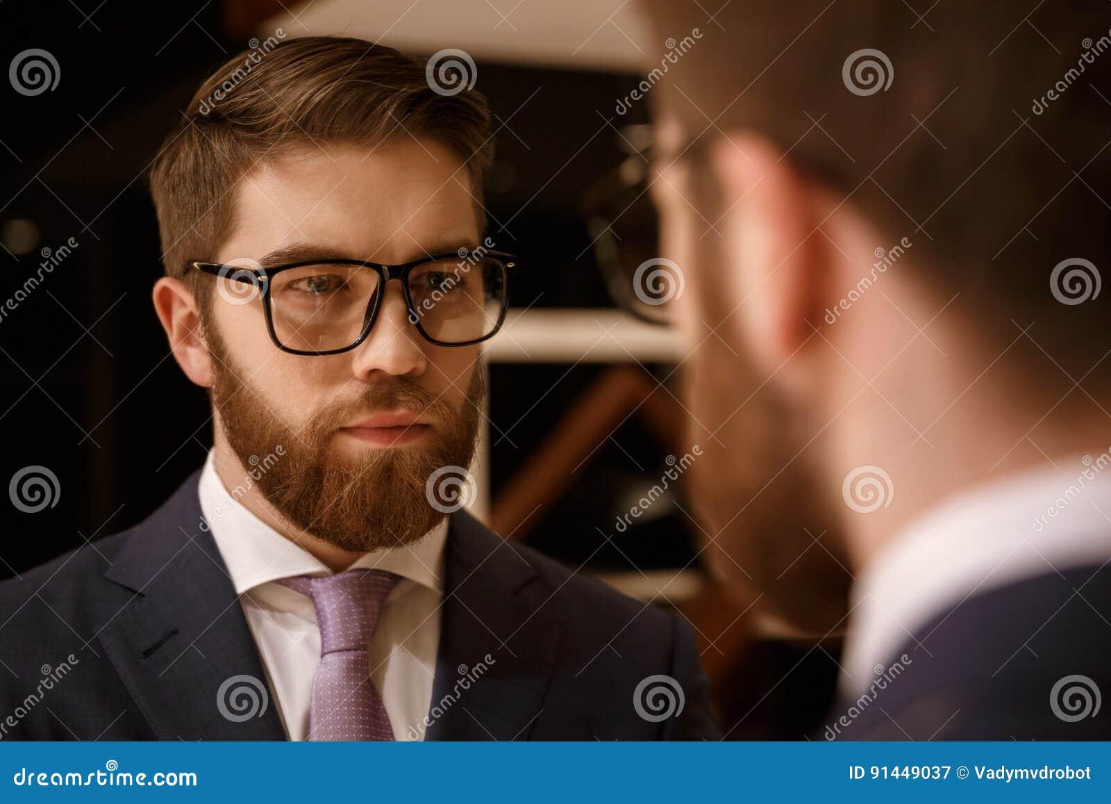 Skoncentrowany młody brodaty biznesmen patrzeje lustro