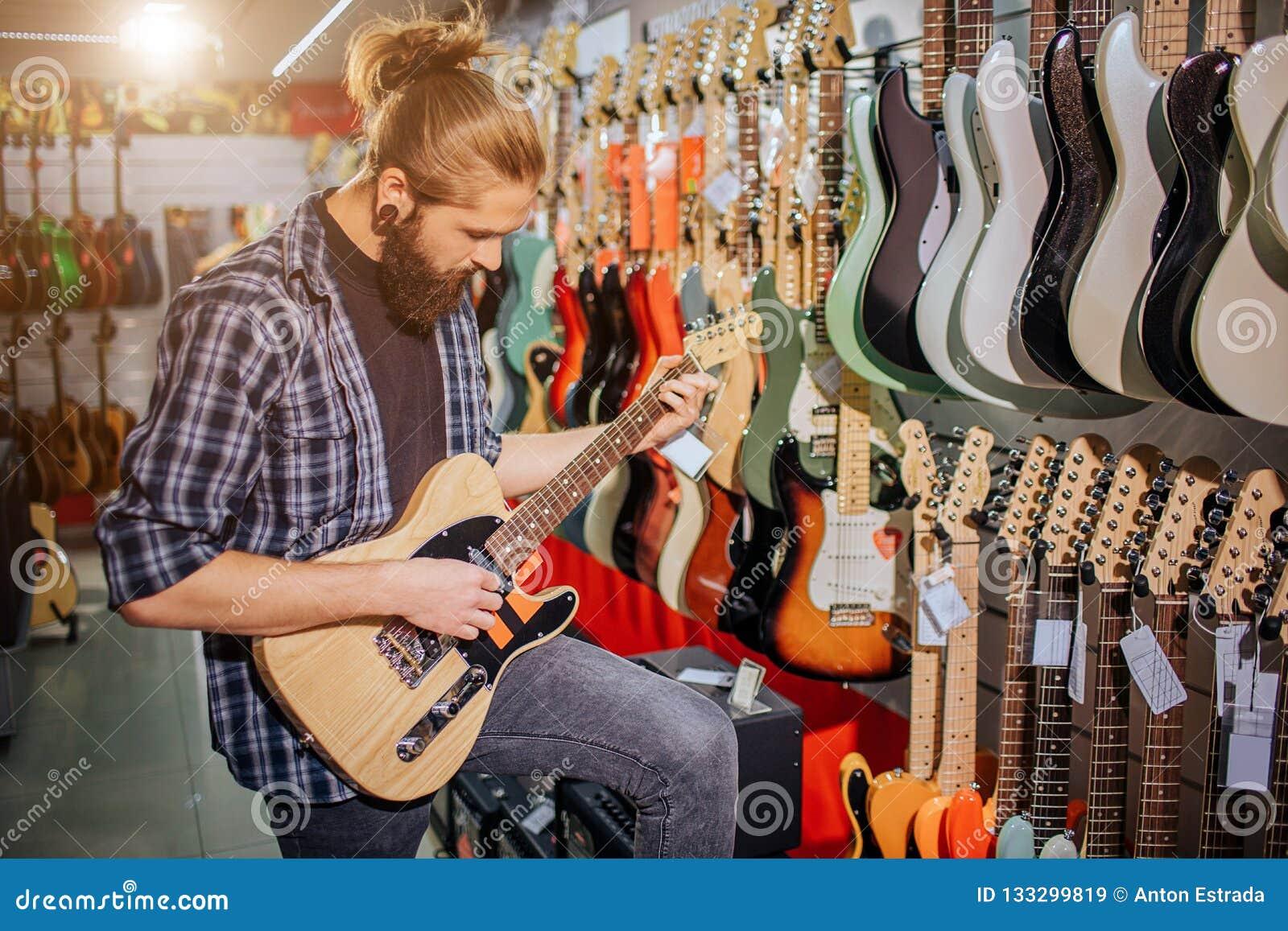 Skoncentrowany młody muzyka stojak, sztuka na gitarze elektrycznej i Patrzeje mnie Facet jest w muzyka sklepie Młody modniś
