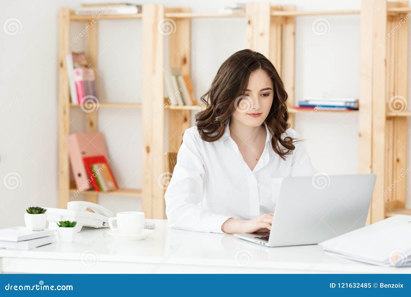 Skoncentrowany młody piękny bizneswoman pracuje na laptopie i dokumencie w jaskrawym nowożytnym biurze