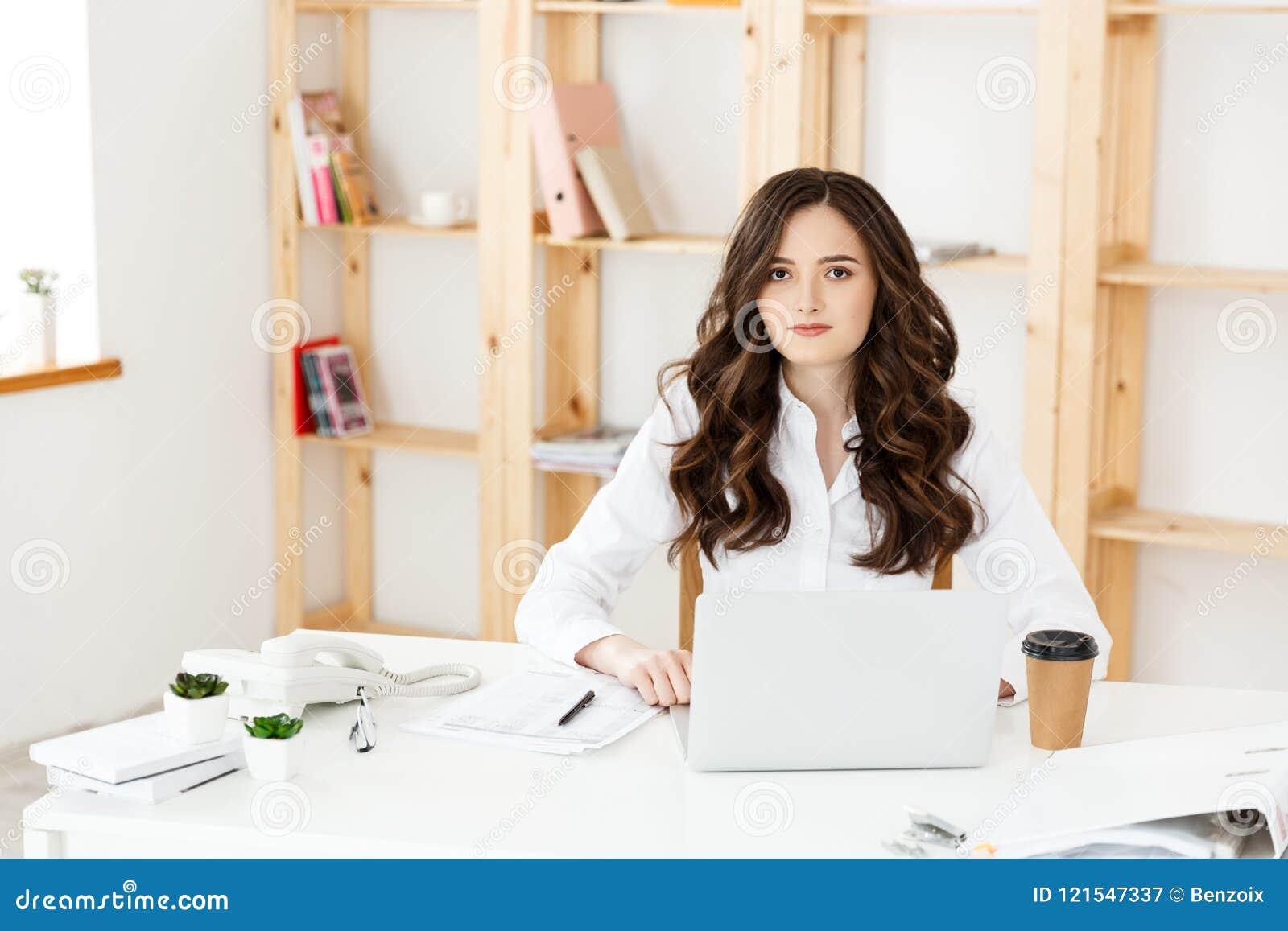 Skoncentrowany młody piękny bizneswoman pracuje na laptopie w jaskrawym nowożytnym biurze