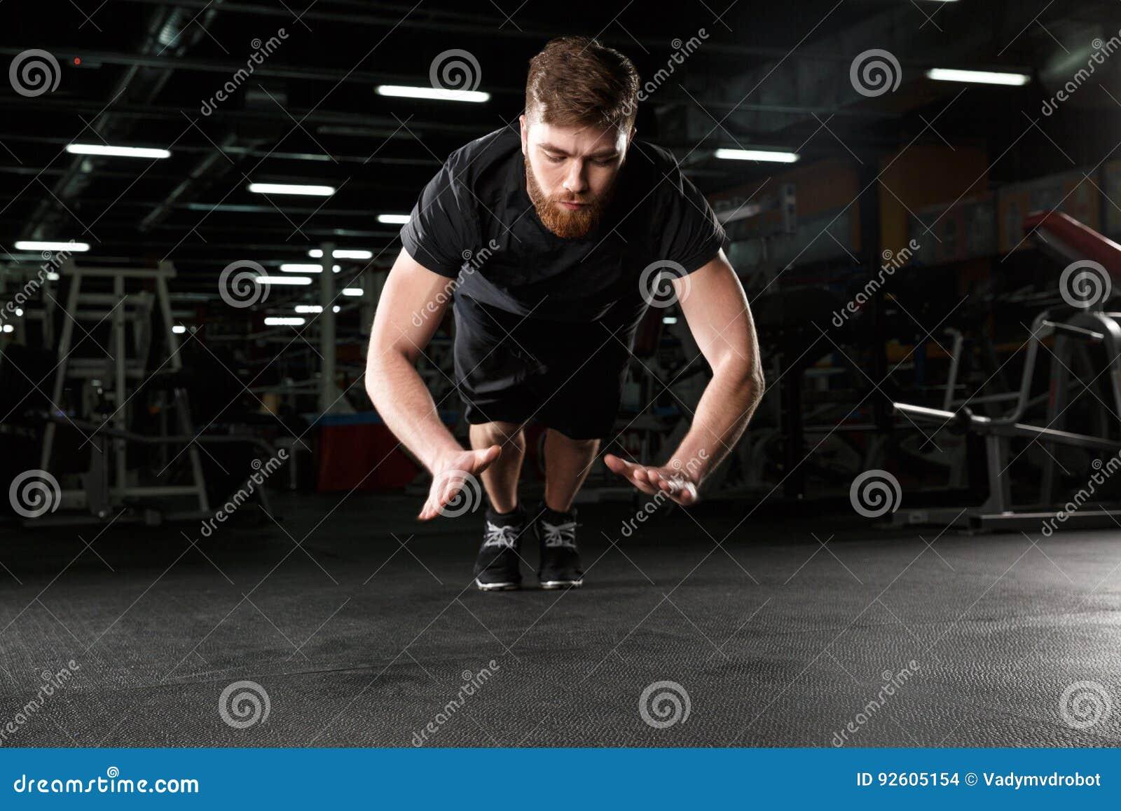 Skoncentrowany młody silny sporta mężczyzna robi sportowi ćwiczyć