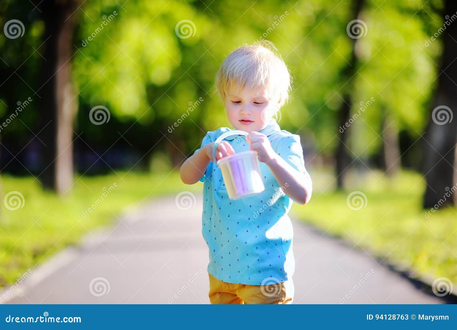 Skoncentrowany małe dziecko chłopiec rysunek z barwioną kredą na asfalcie
