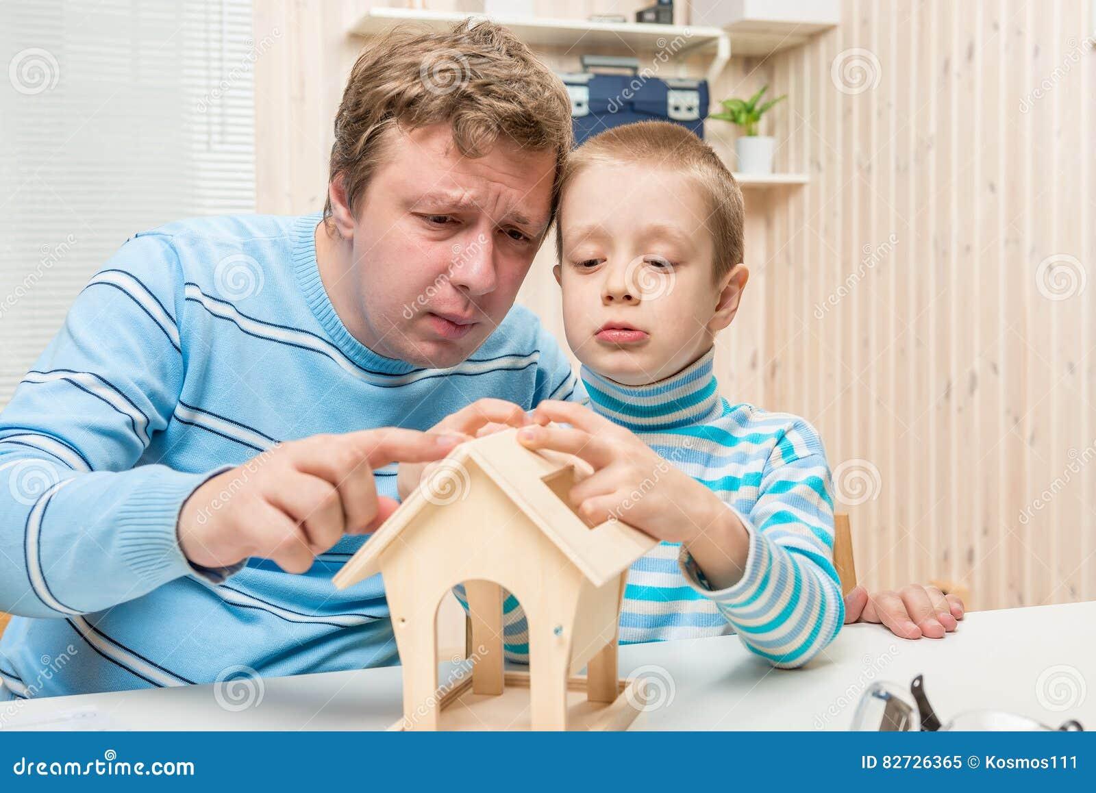 Skoncentrowany ojciec i syn buduje ptasiego dozownika