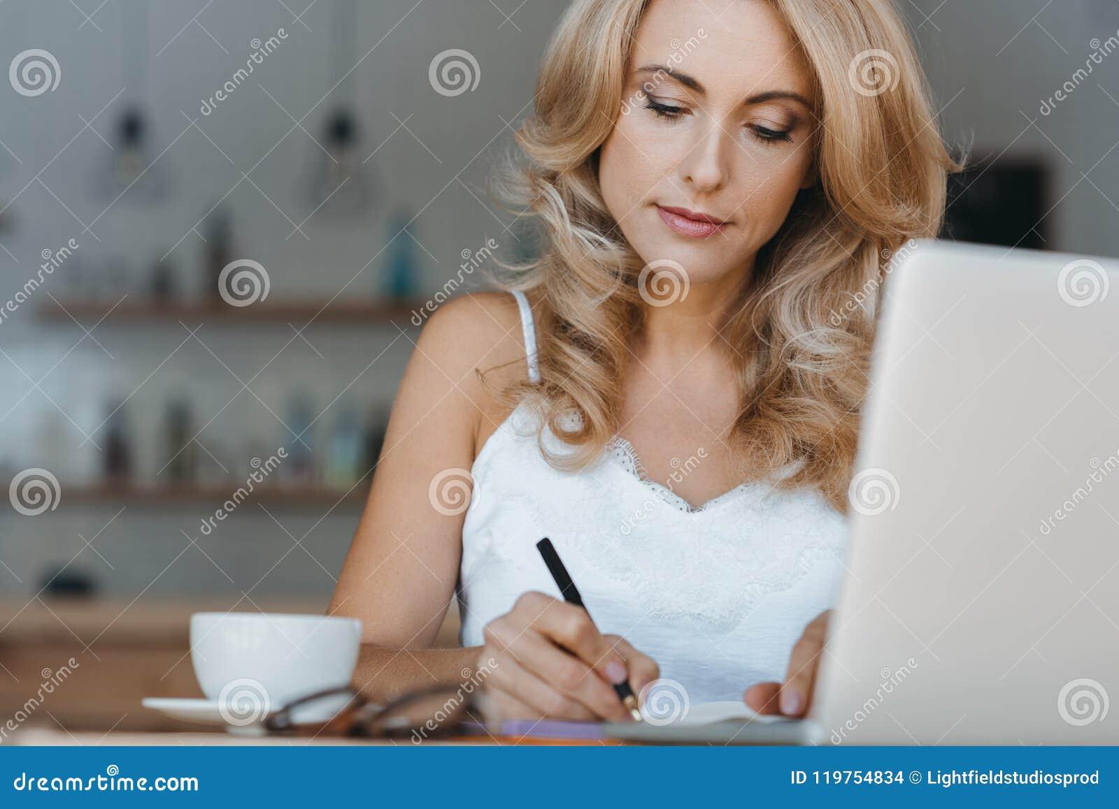 Skoncentrowany w średnim wieku bizneswoman używa laptop i brać notatkę