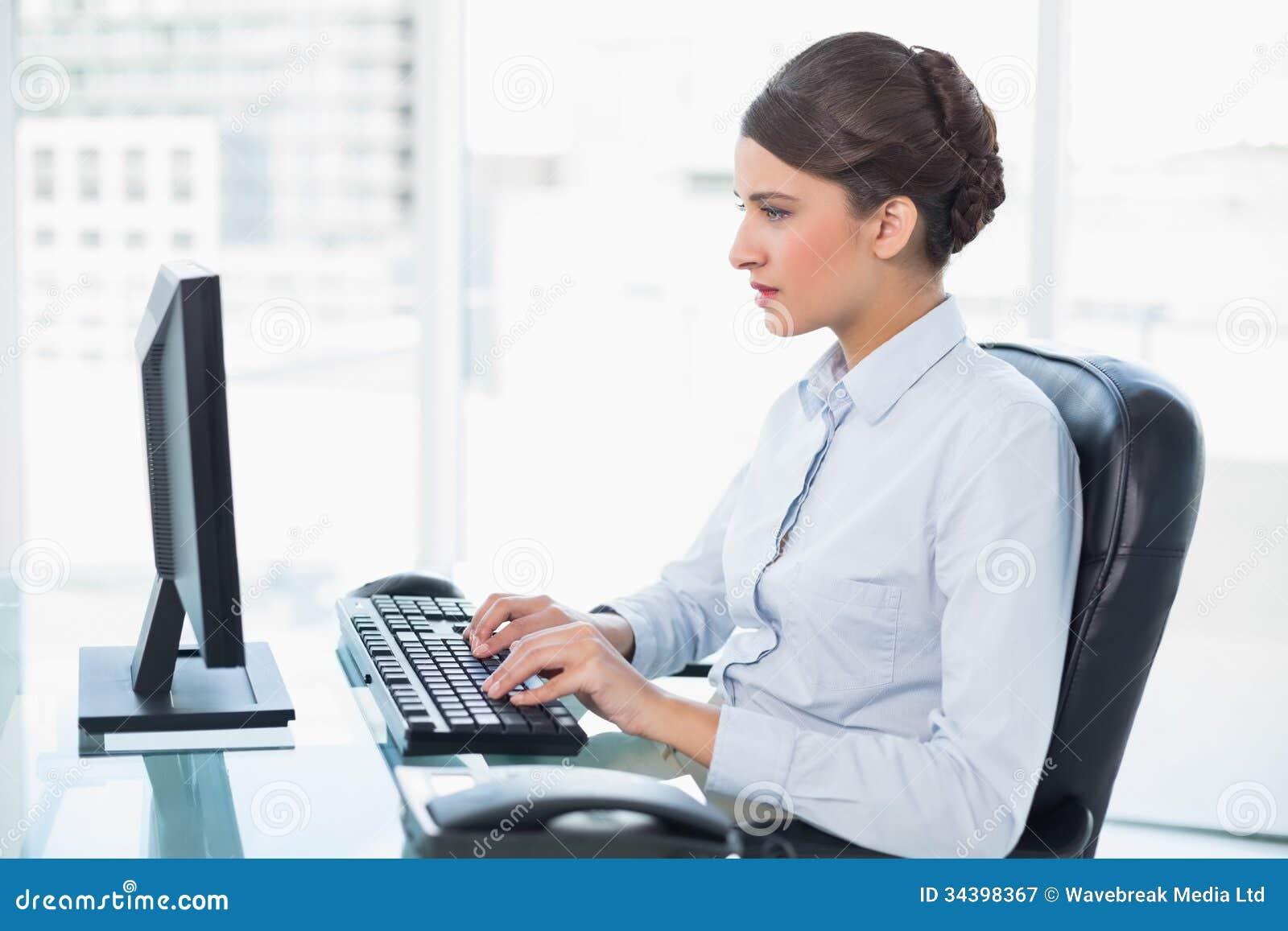 Skoncentrowany z klasą brown z włosami bizneswoman pisać na maszynie na komputerze