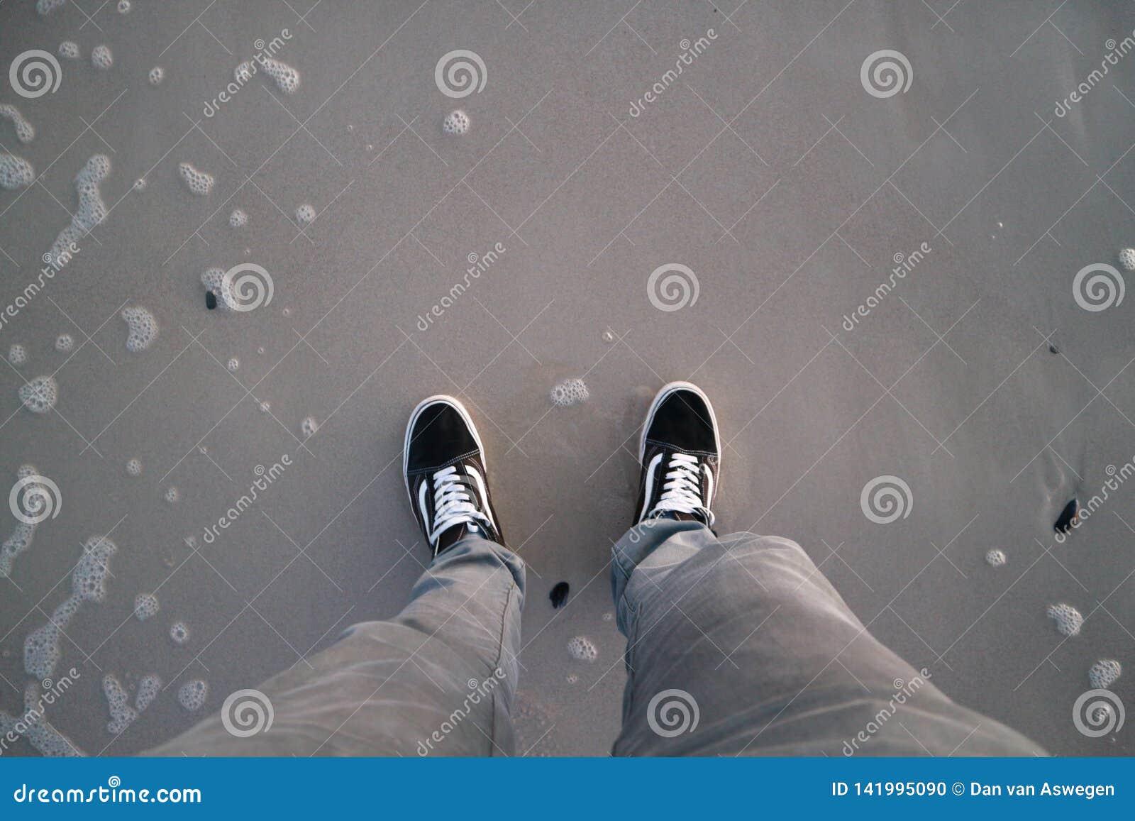 Skor på stranden som bara står den svarta skridskon