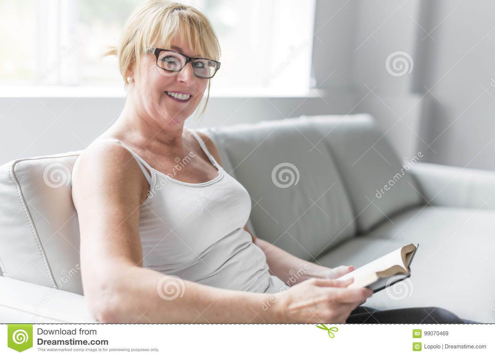 Skott av en mogen kvinna som läser hennes favorit- roman medan hemma i vardagsrum