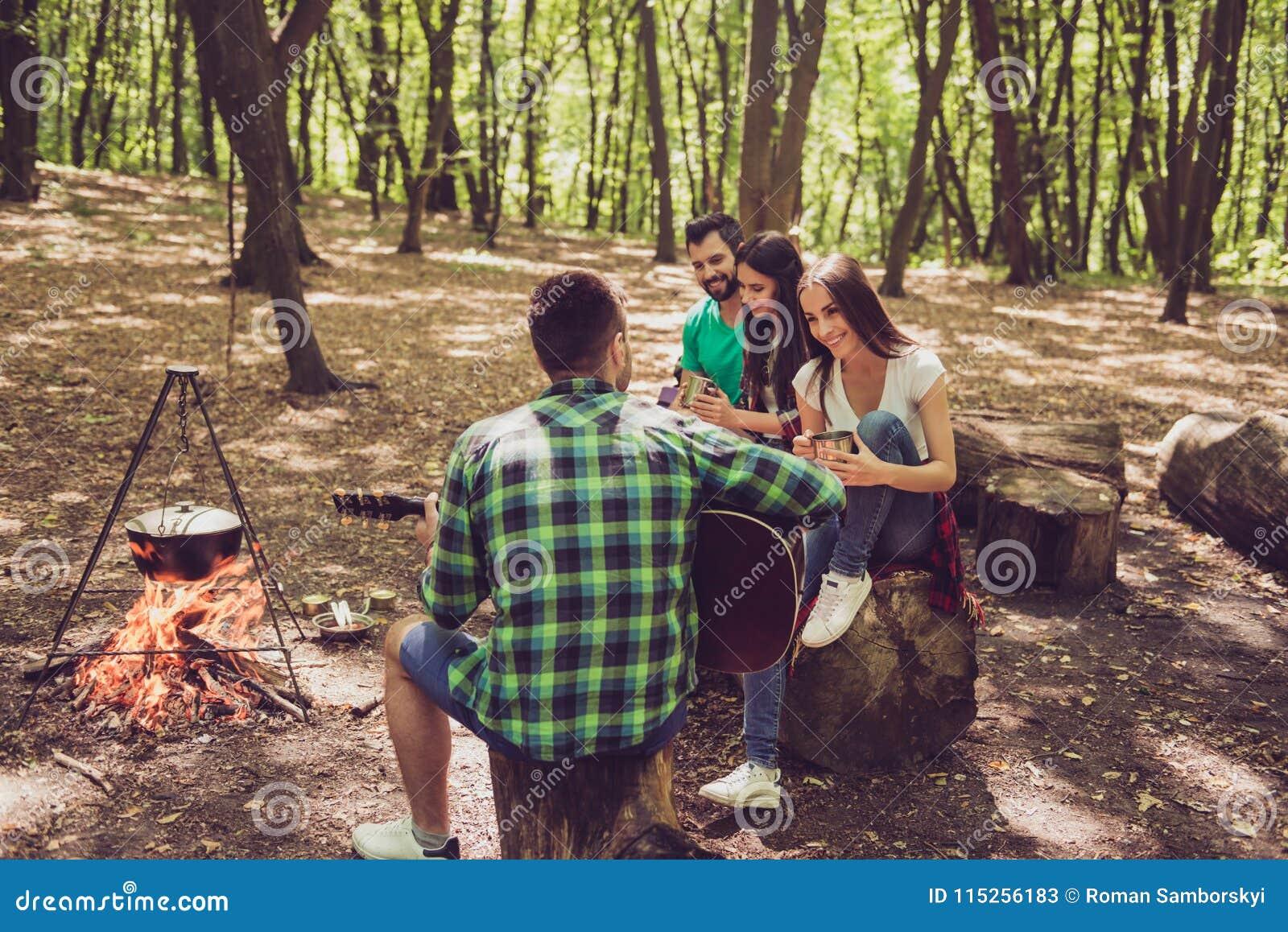 Skott för bakre sikt av grabben som spelar gitarren i den wood near branden Thre