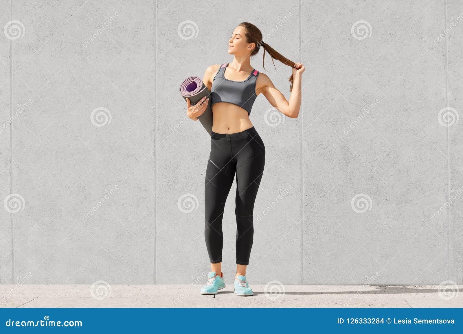 Skottet av den slanka härliga idrottskvinnan med sportig kroppform, bär sportswearen, rymmer ponnysvansen som går till kondition