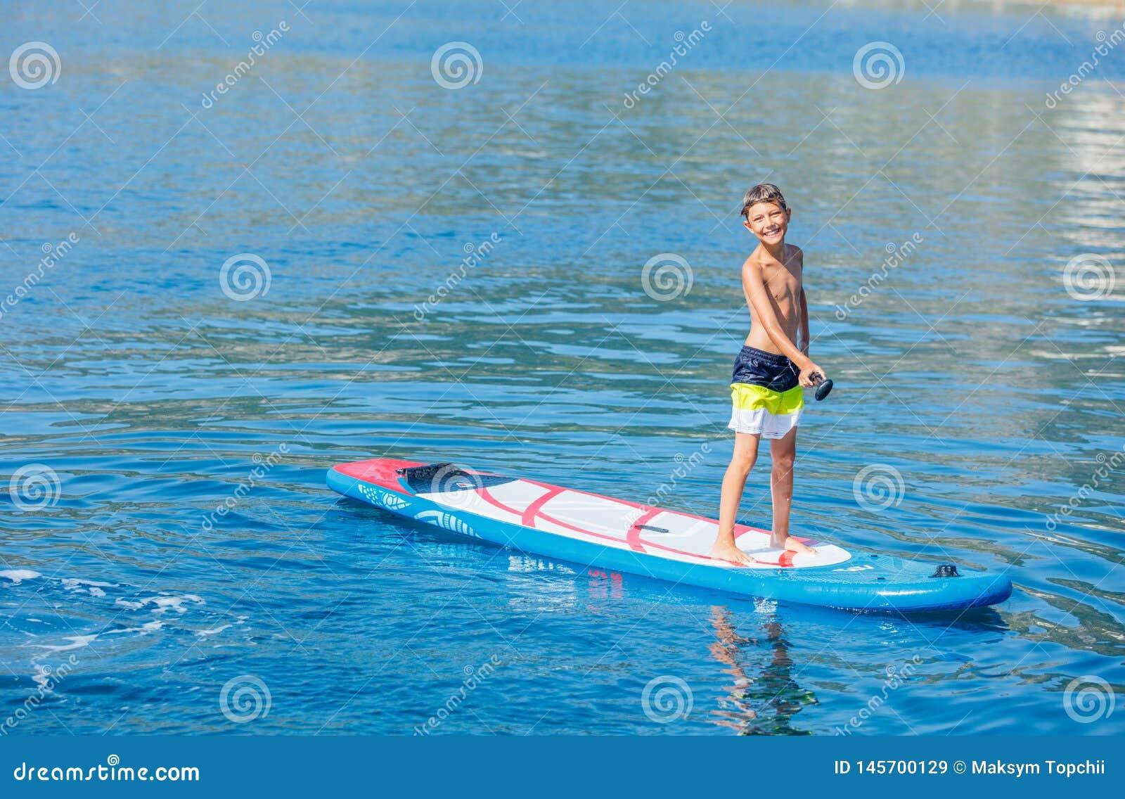 Skovelboarder Barnpojke som paddlar på paddleboard för ställning upp Sund livsstil Vattensporten, att surfa för SUP turnerar
