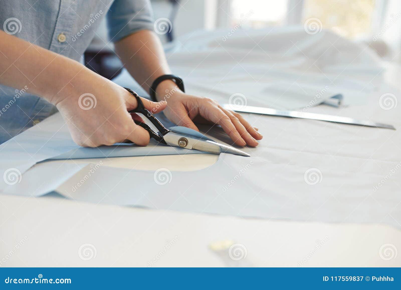 Skräddare Hands Cutting Material med sax på tabellen