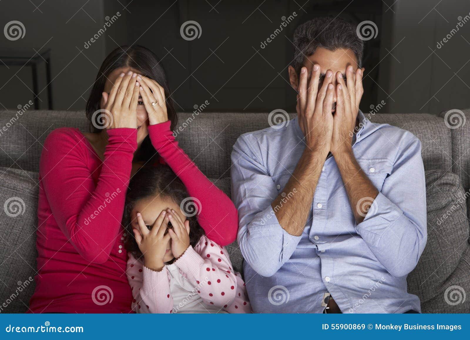 Skrämt latinamerikanskt familjsammanträde på Sofa And Watching TV