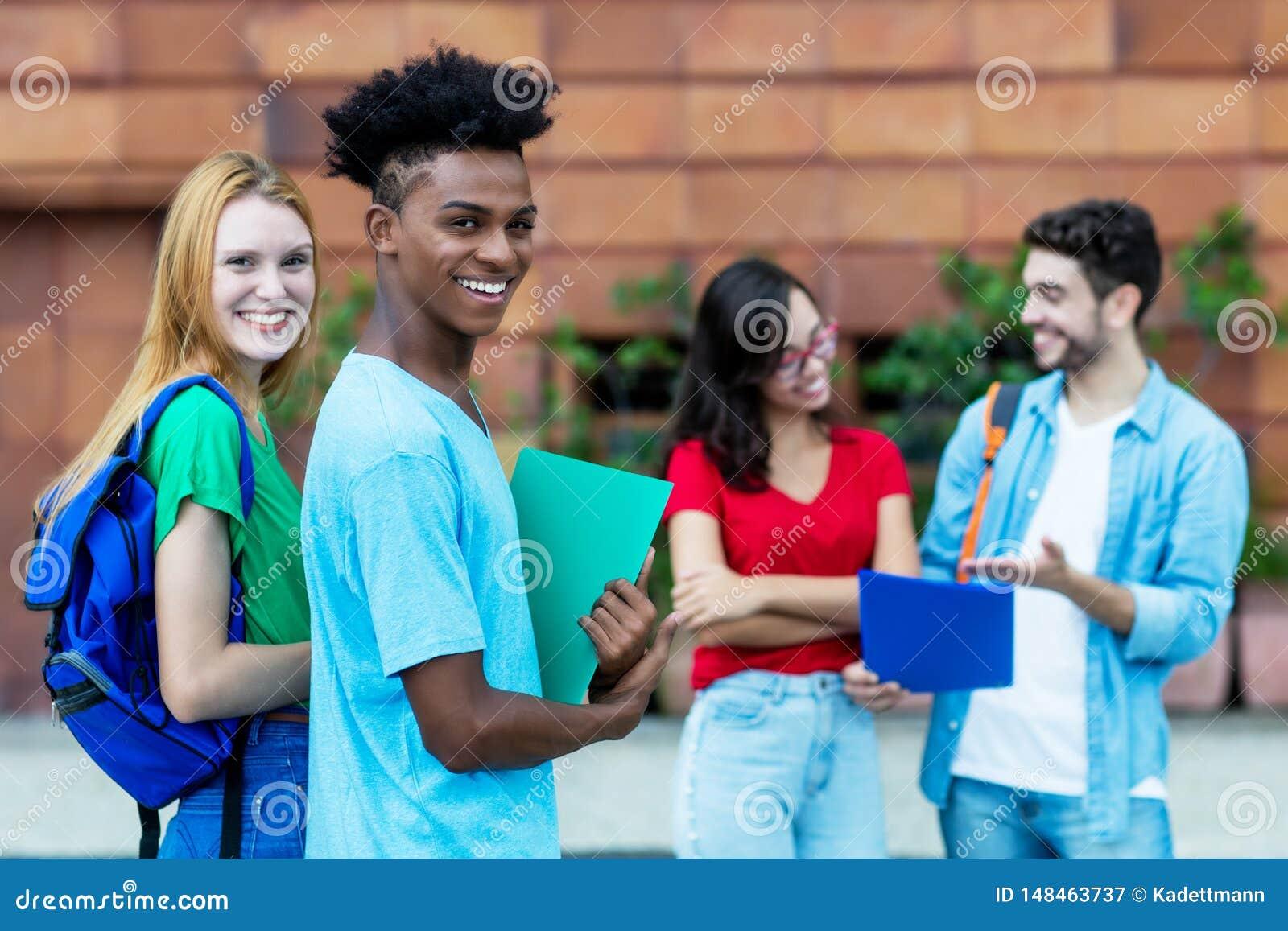 Skratta den caucasian manliga studenten för kvinnlig och för afrikansk amerikan