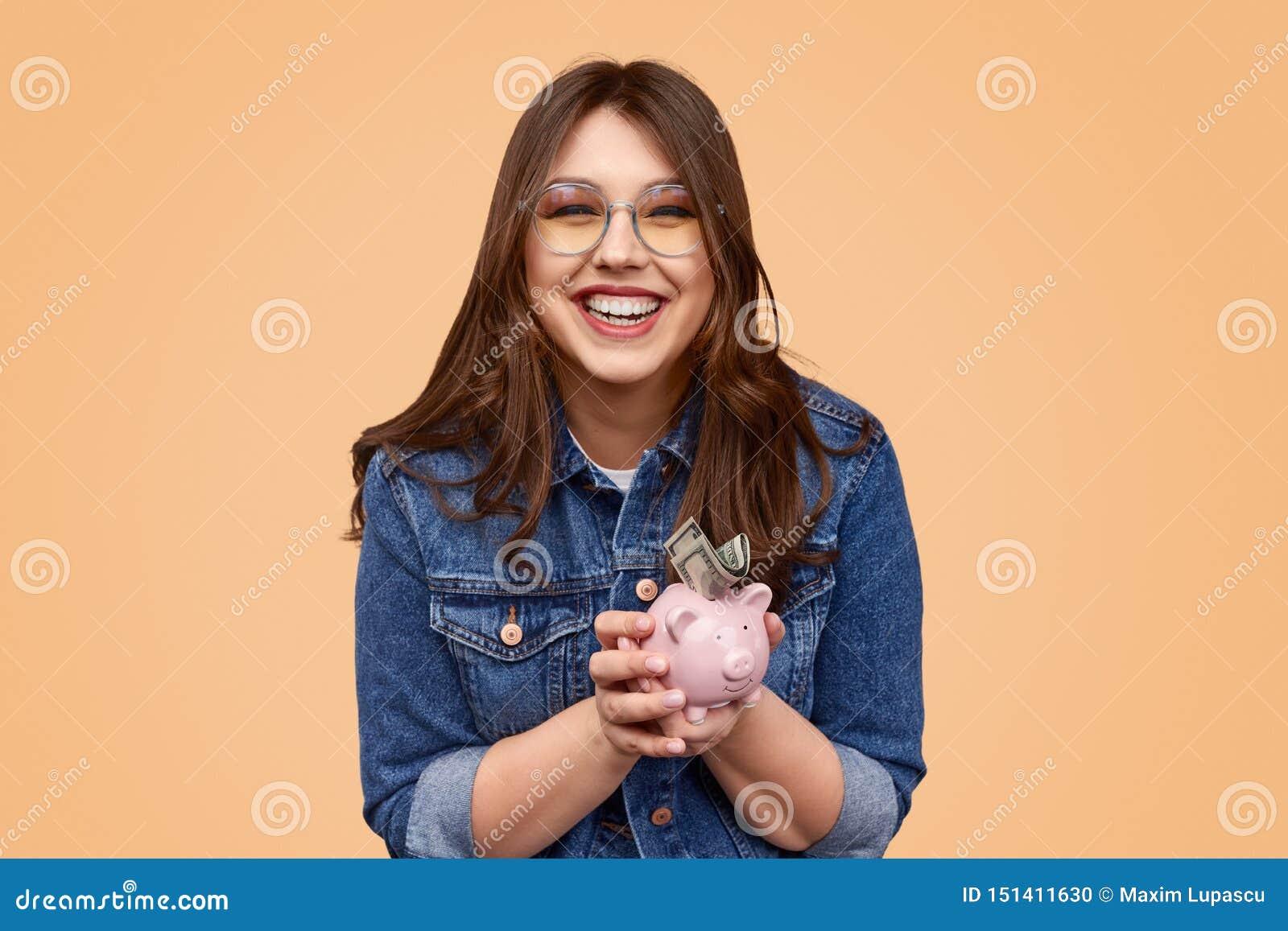 Skratta den knubbiga kvinnan som sätter pengar i spargrisen