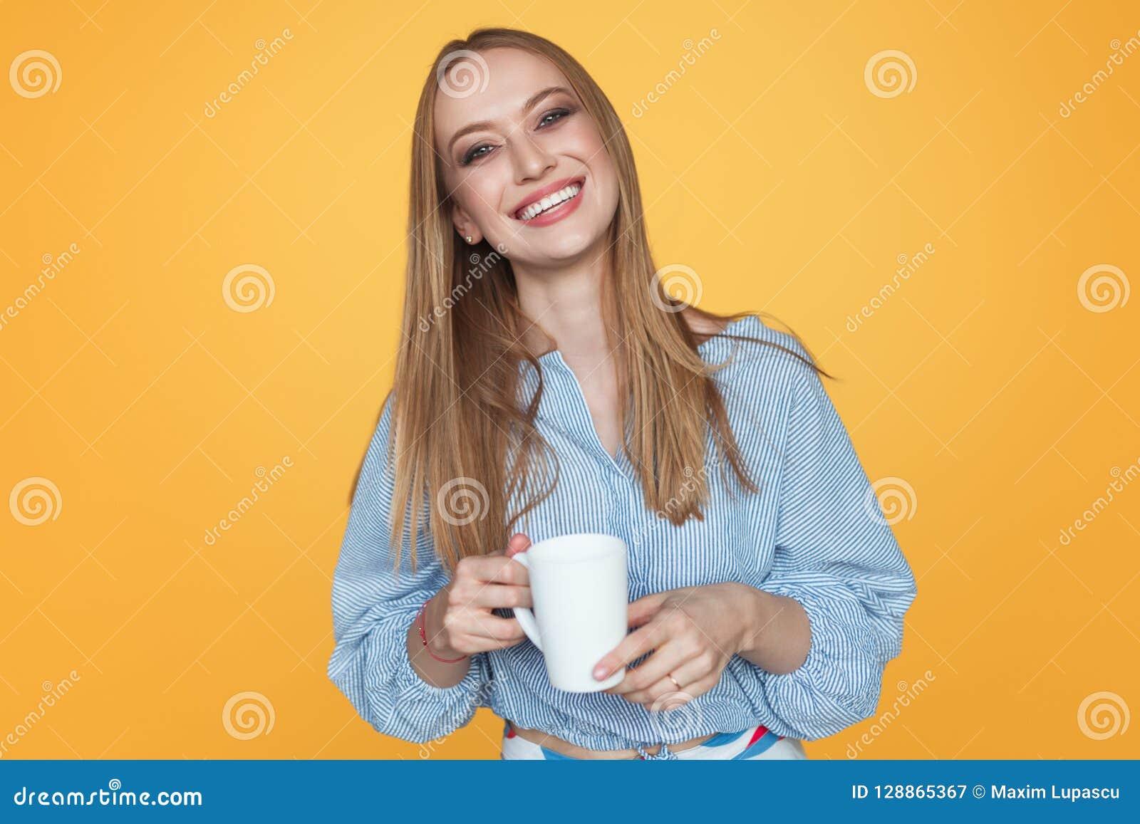 Skratta den moderiktiga kvinnan med kaffe råna