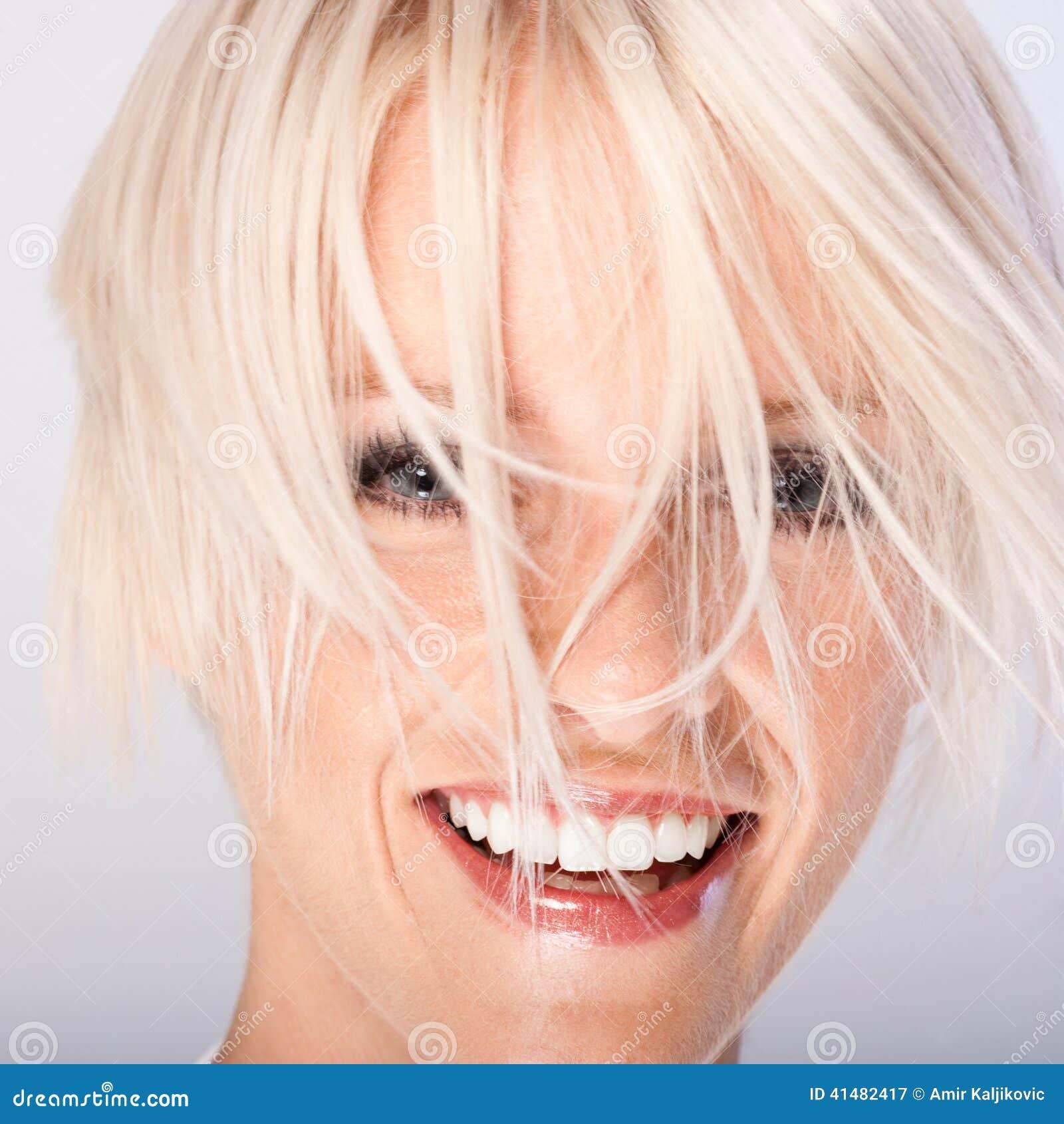 Skratta den unga kvinnan med skraj blont hår