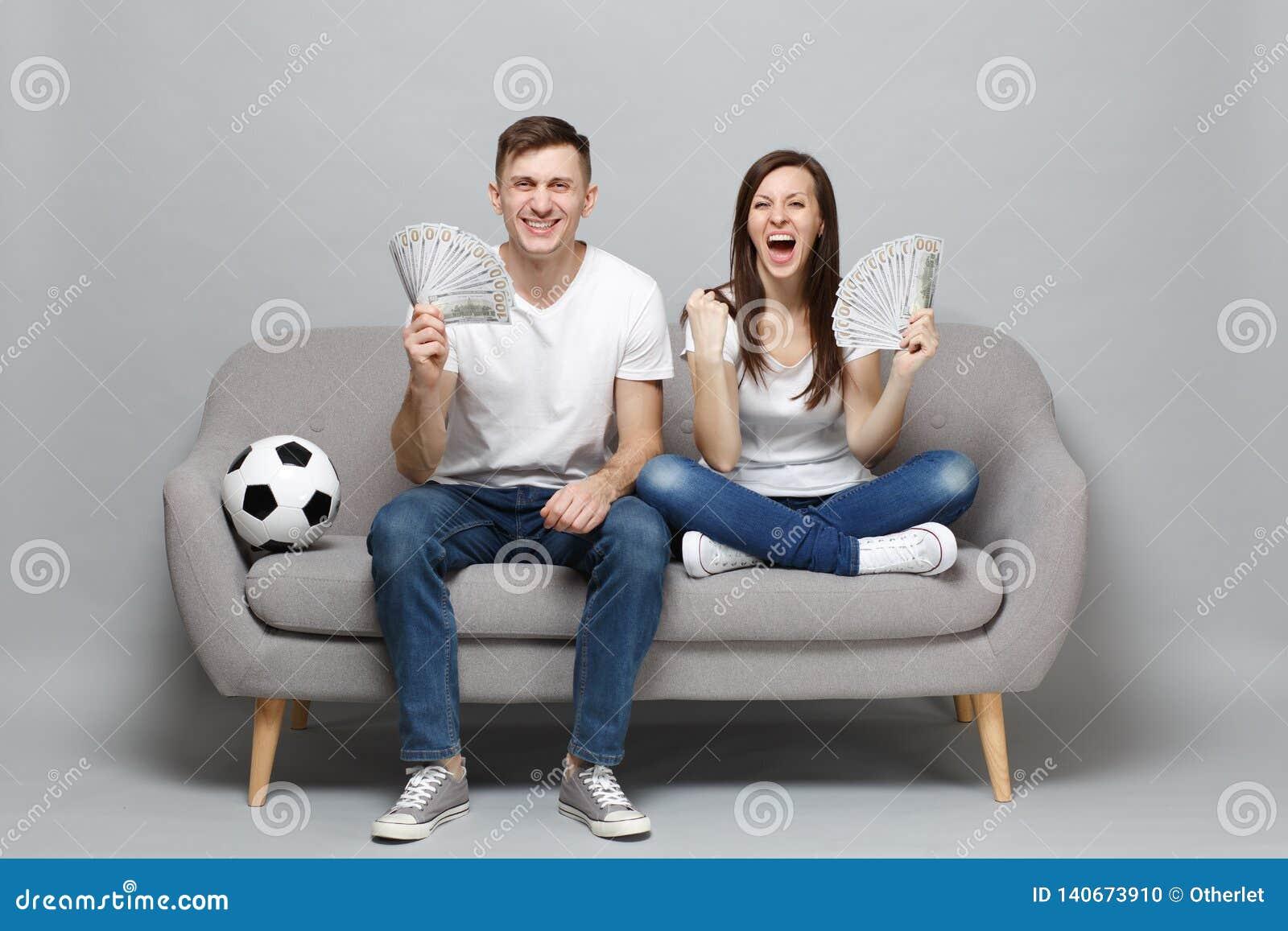 Skratta fotbollsfan för parkvinnamannen hurra upp det favorit- laget för service som rymmer fanen av pengar i dollarsedlar, kassa