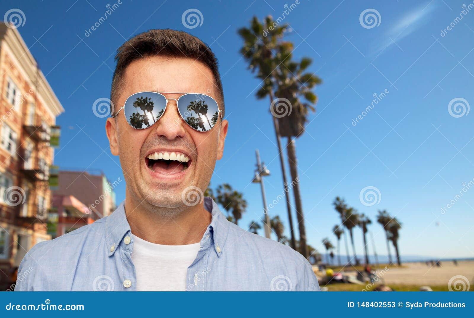 Skratta mannen i solglasögon över den venice stranden