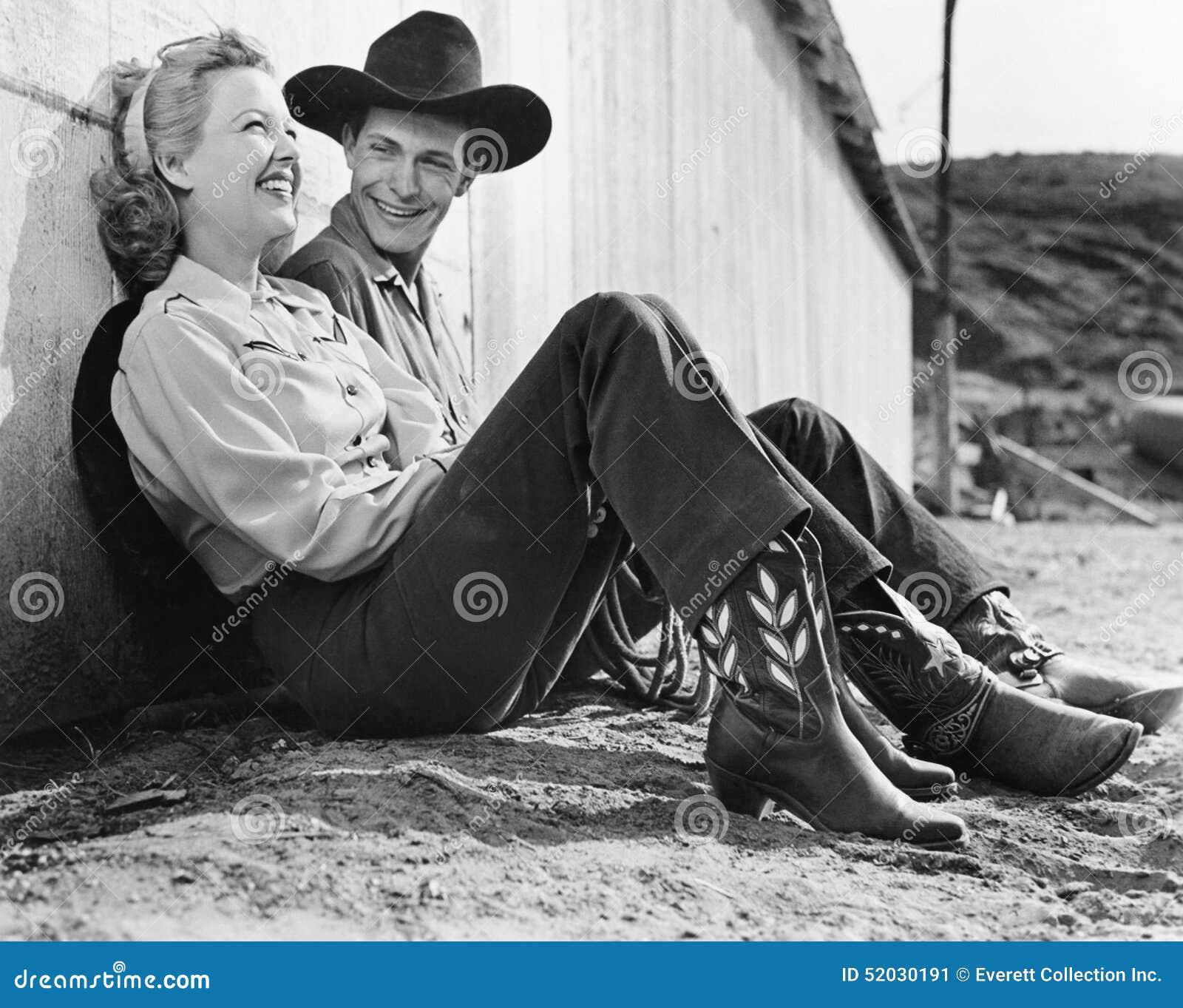 Skratta par i västra dresssammanträde på jordningen (alla visade personer inte är längre uppehälle, och inget gods finns Suppli