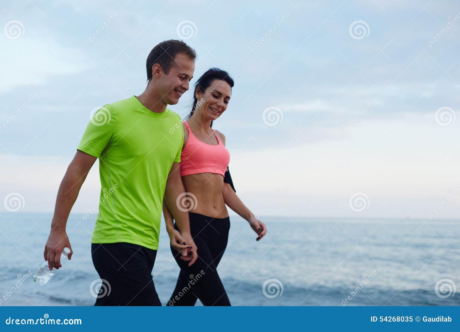 Skratta par promenera kusten efter konditionutbildning