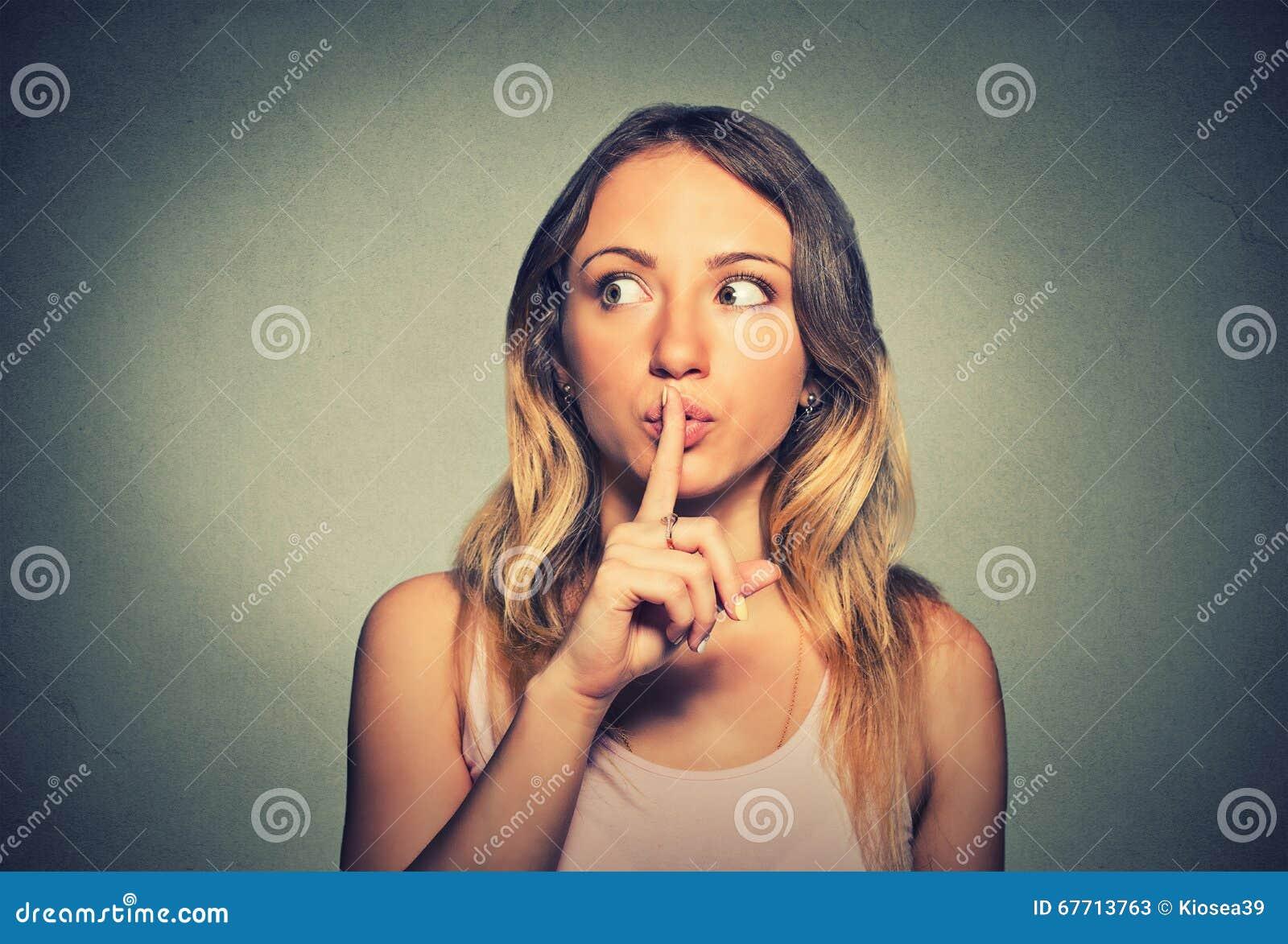 Skryta kobieta umieszcza palec na wargach pyta shh, zaciszność