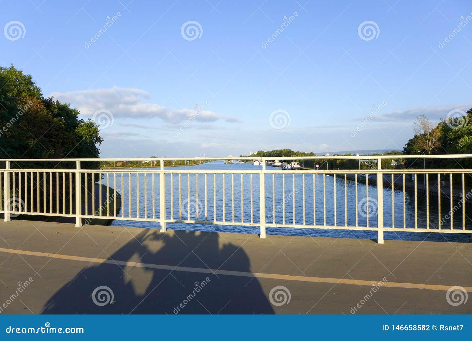 Skugga av en moped på en bro