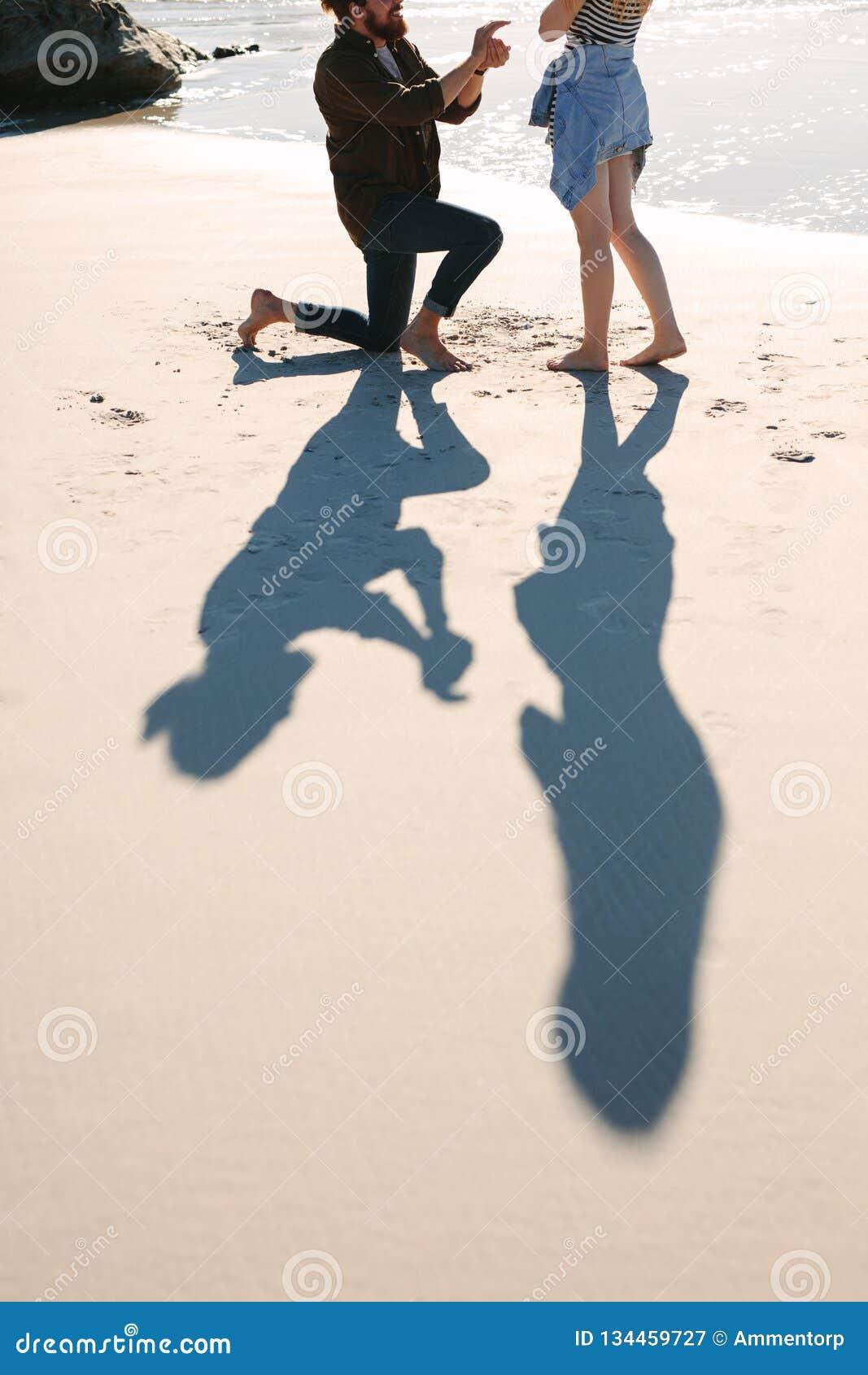 Skugga av mannen som föreslår kvinnan på stranden