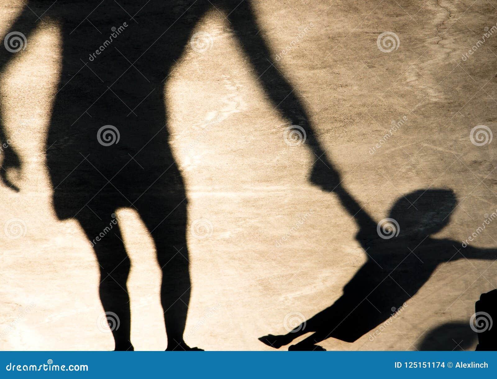Skuggar konturer av modern och barnet på sommarpromenad