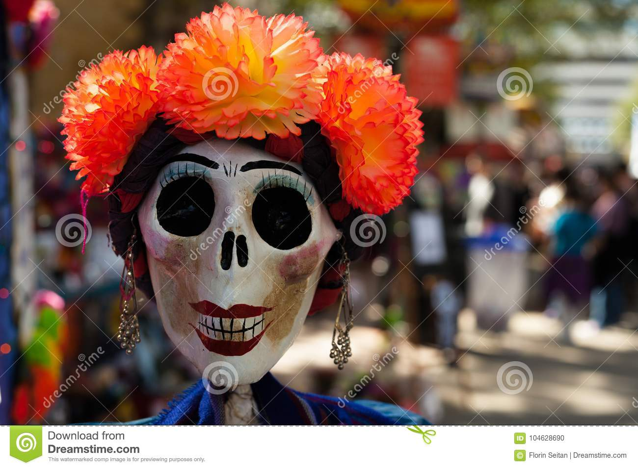 Skull painted and decorated with orange paper mache flowers and earrings/decorated skull for Dia de los Muertos, Day of the Dead
