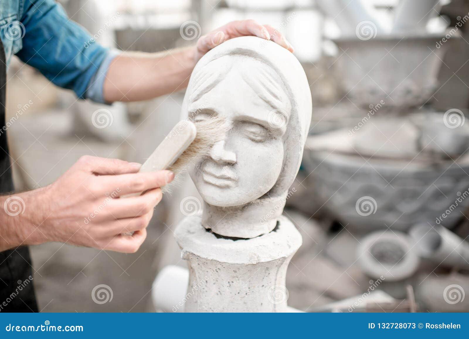 Skulptör som arbetar med skulptur i studion