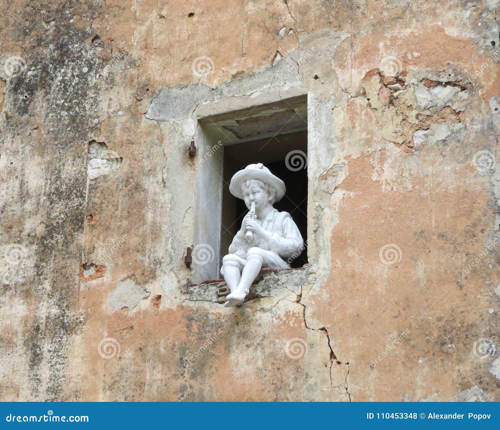 Skulptur en pojke som spelar flöjten
