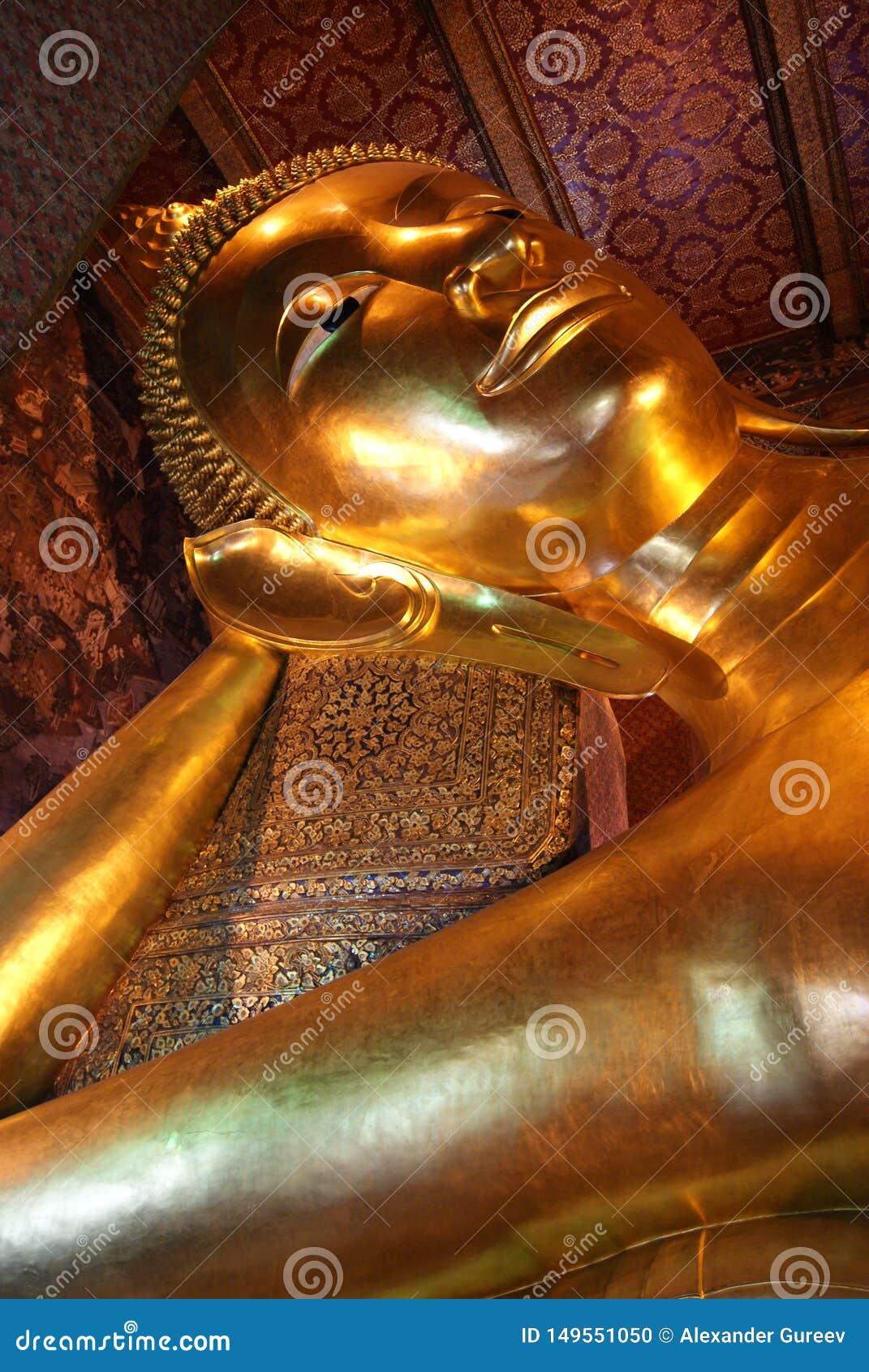Skulpturen av den guld- Buddha för vila thailand
