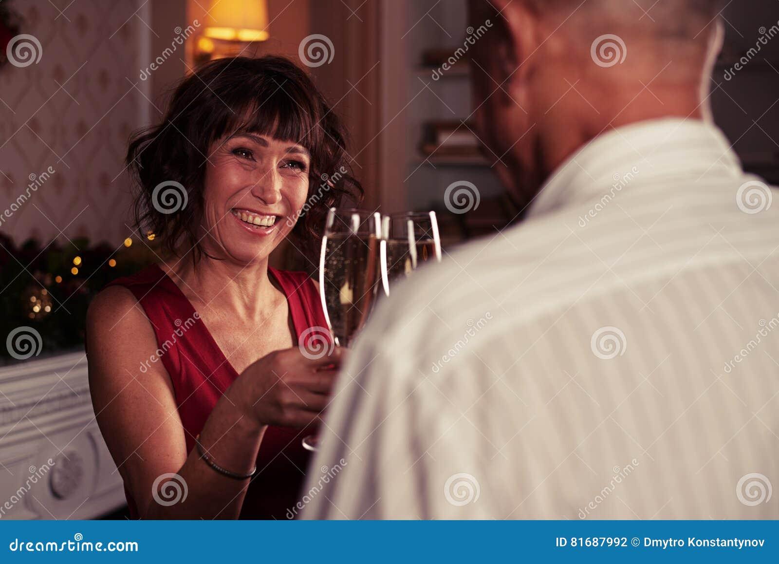 Skupia się na szczęśliwej starszej kobiecie clinking glasse szampan z