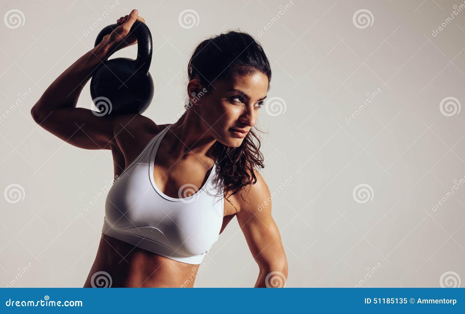 Skupiająca się młoda kobieta robi crossfit