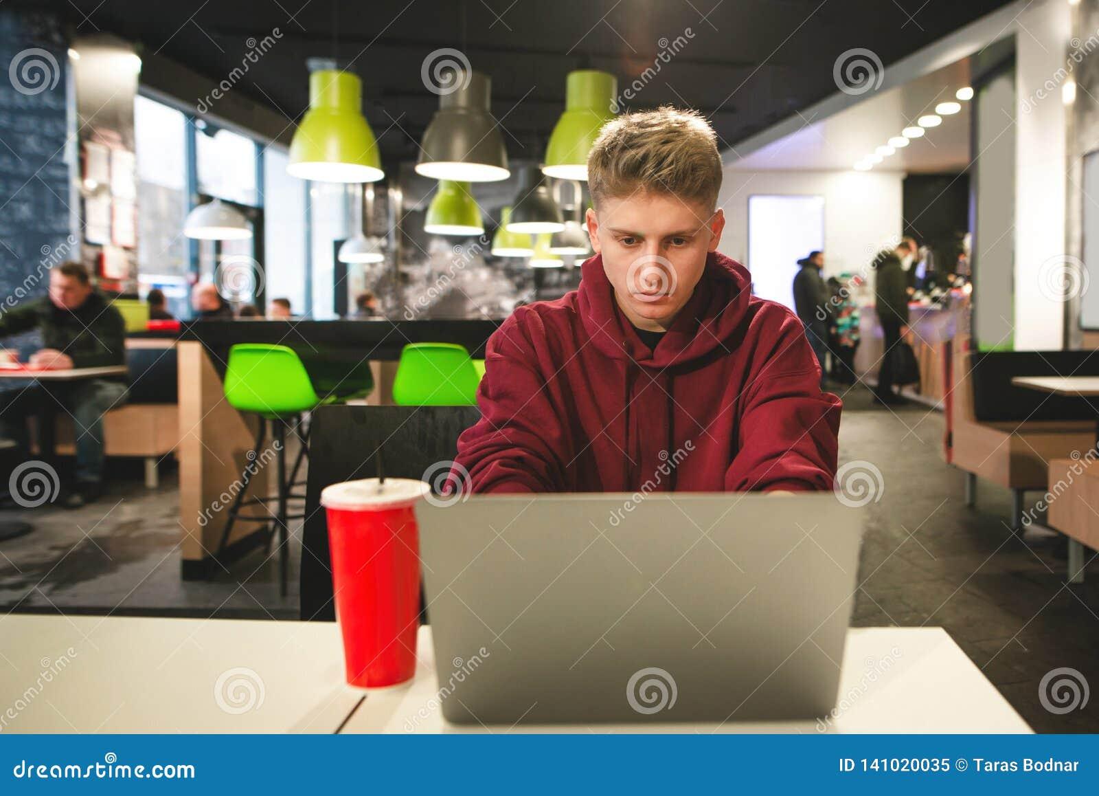 Skupiający się faceta freelancer pracuje na laptopie w fast food kawiarni, skupia się na ekranie