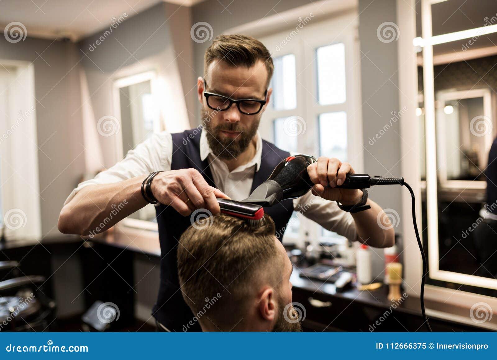 Skupiający się fryzjera męskiego klienta suszarniczy włosy