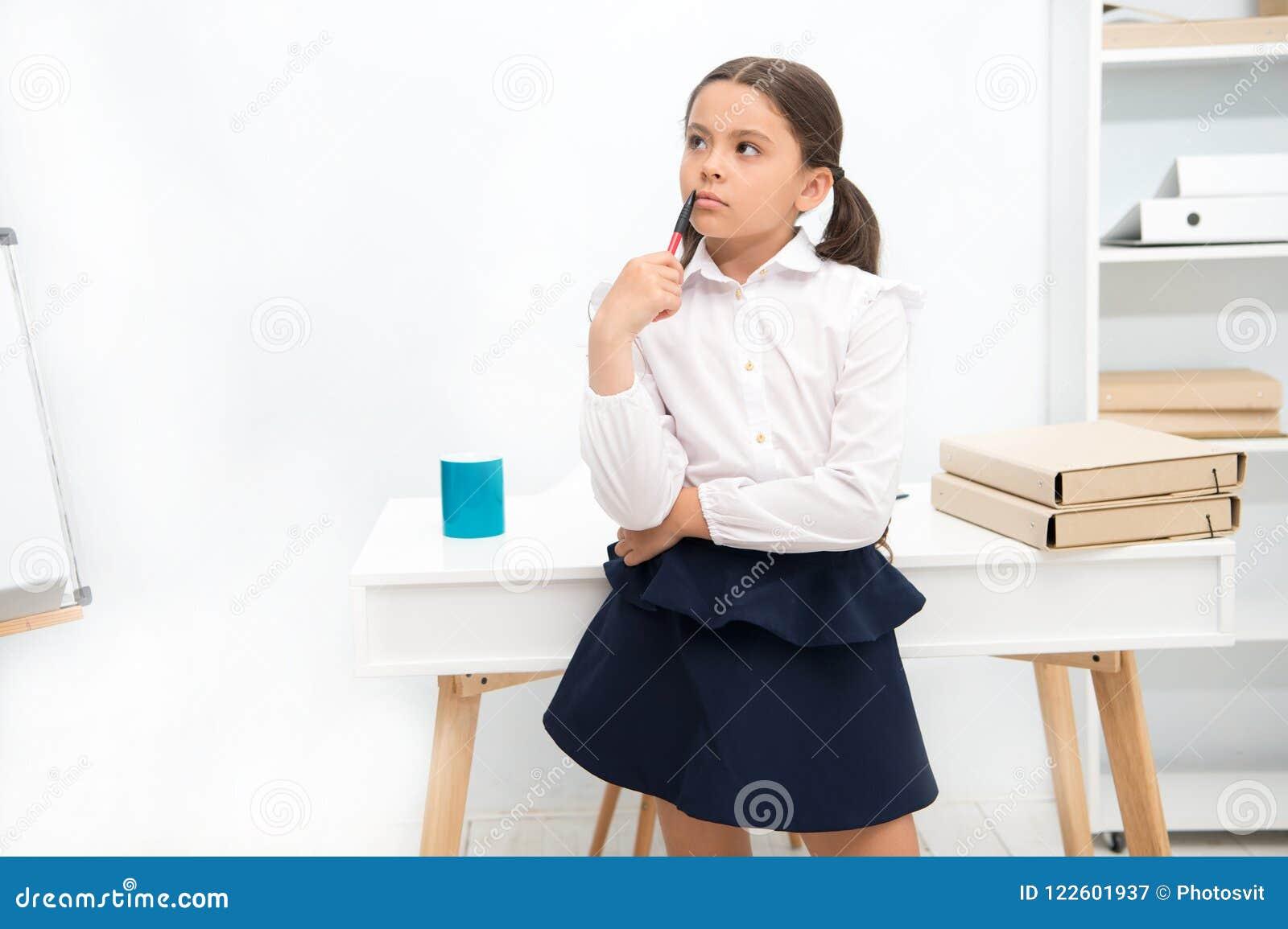 Skupiający się na pamiętać Dziecko dziewczyna jest ubranym mundurek szkolny pozycję z pamiętać twarzy wyrażenie Uczennica mądrze