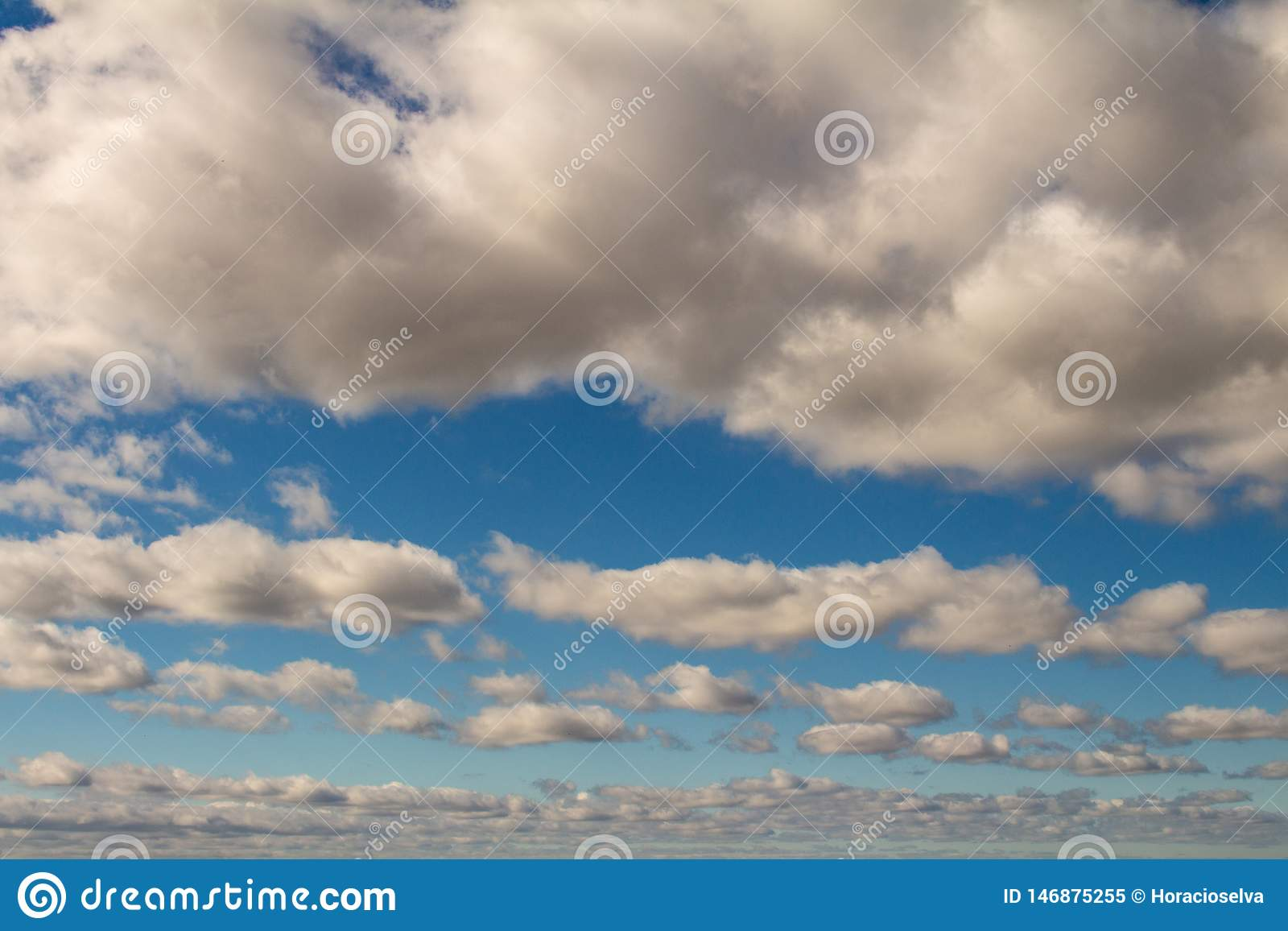 Sky of abundant white clouds and celestial spaces. Cottony clouds distributed throughout the sky