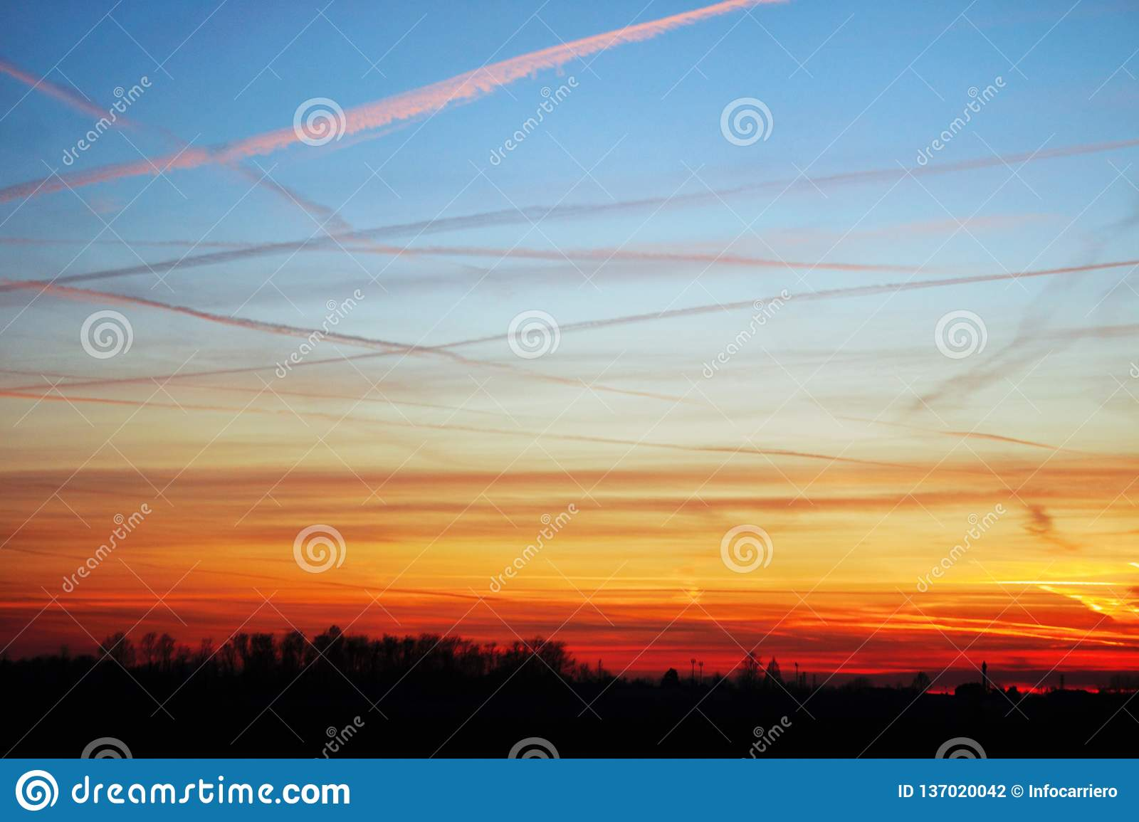 sky at sunset, the clouds are colored red by the sun that in a while will make room for the moon