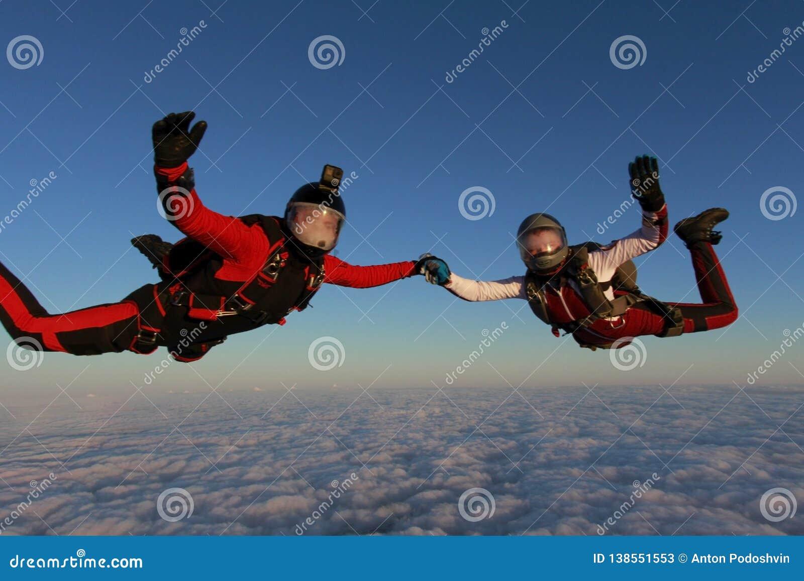 Skydiving Dos skydivers están volando en el cielo de la puesta del sol
