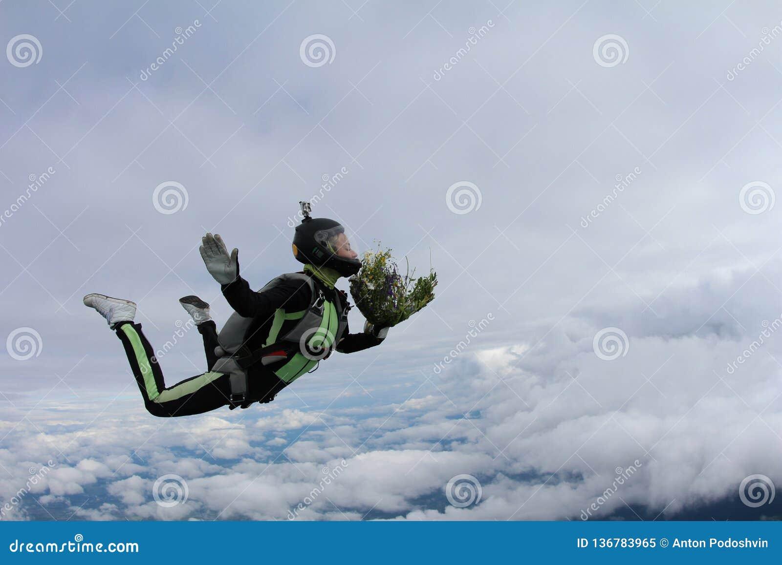 Skydiving Ragazza con il mazzo di fiori nel cielo