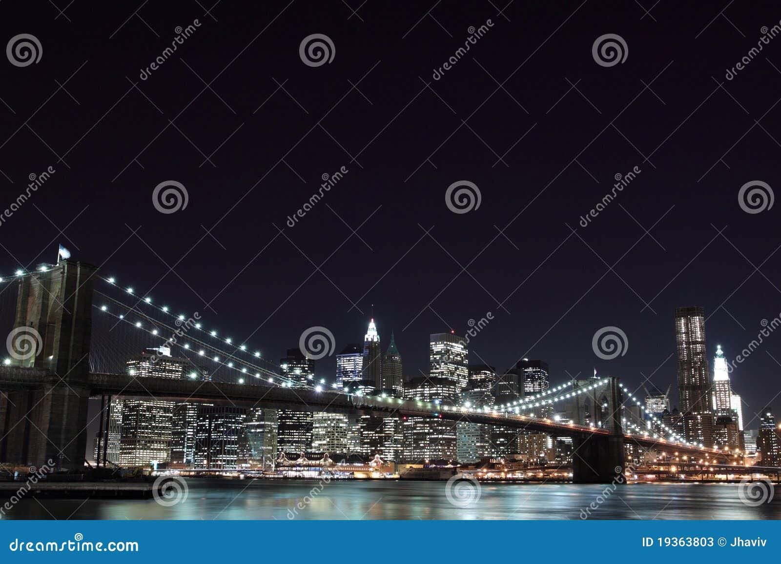 Skyline da ponte e do Manhattan de Brooklyn na noite