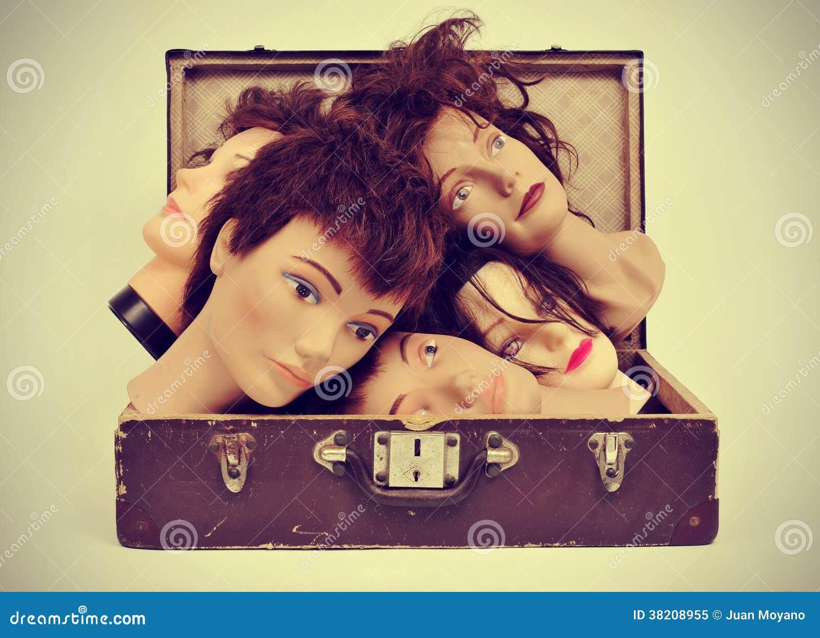 Skyltdockahuvud i en gammal resväska
