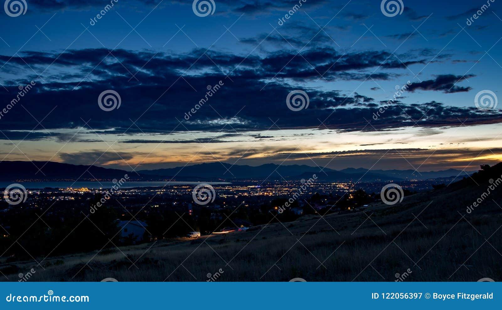 Skymning faller över en sömnig stad i en dal med berg och en sjö i bakgrunden